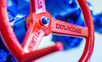 A red handle manufactured by Downing is shown attached to blue fracking equipment.